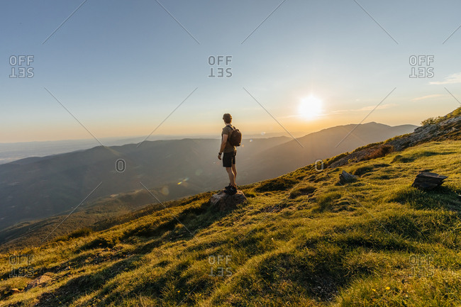 Back view of young man with back pack contemplating amazing mountain landscape on the countryside