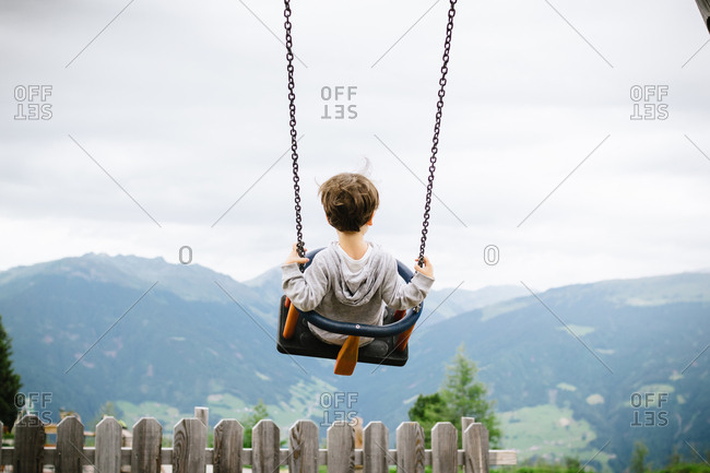 Back view of active kid swinging high in countryside on background of breathtaking mountains in cloudy day
