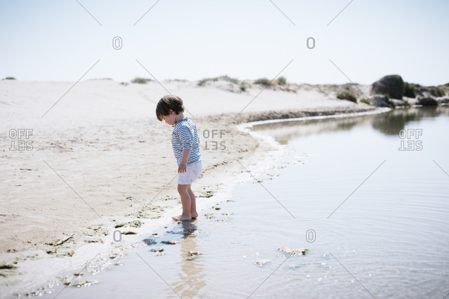 Side view of cute baby standing with bare feet in sand and looking at shiny calm sea in beautiful beach in sunny day