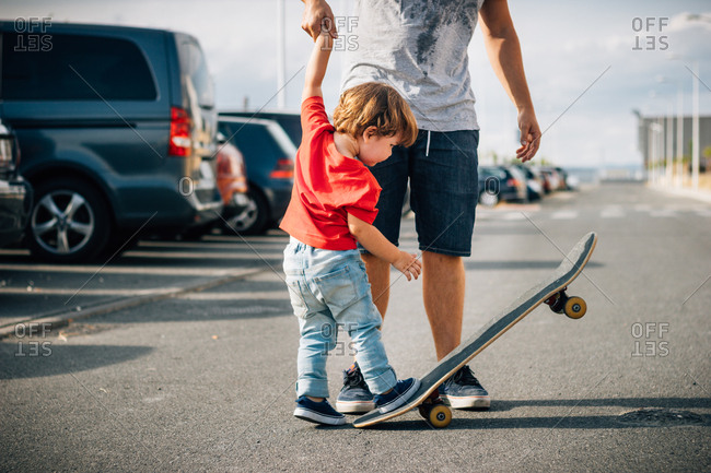 Young man in short holding hands with kid in red t-shirt and helping to skateboard on road in sunny day
