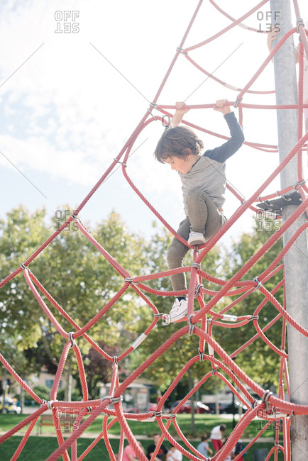 Small boy hanging on rope while walking climbing net on playground in bright light