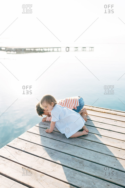 Adorable curious boy with toddler sister sitting on pier observing nature