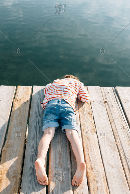 From above of chilling kid lying with face down on wooden pier in sunshine with peaceful water below
