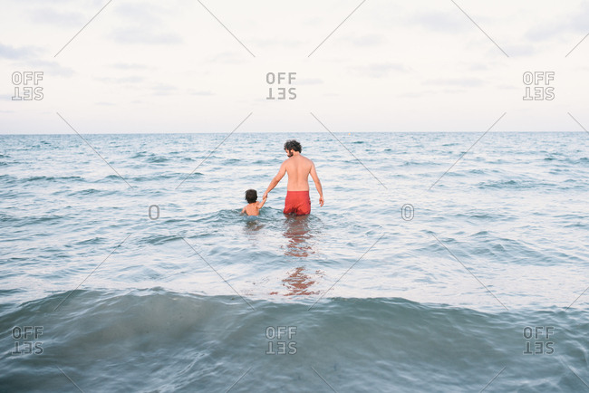 Back view of man with boy holding hands and walking into water swimming together