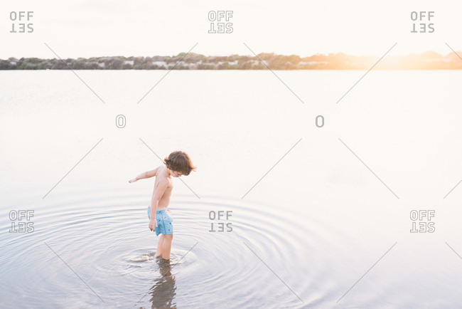 Back view of dreamy boy walking creating ripples in shallow water of beach against sunset light