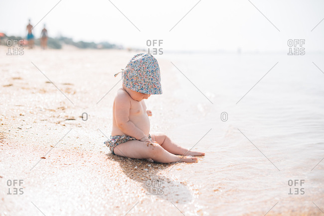 Side view of adorable toddler baby in hat sitting on sandy beach with wave running on in sunshine