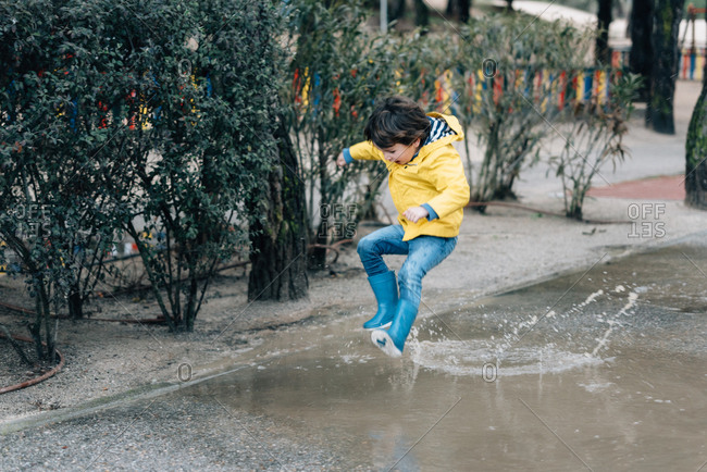 Excited boy in coat and gumboots having fun on street and jumping on puddle