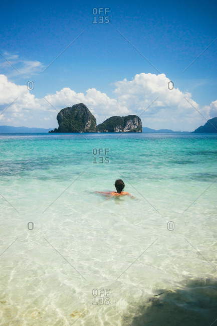 Back view of person lounging in peaceful clear water of ocean against blue sky, Thailand