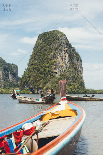 Wooden boats floating on peaceful water of lagoon with green rock on background, Thailand