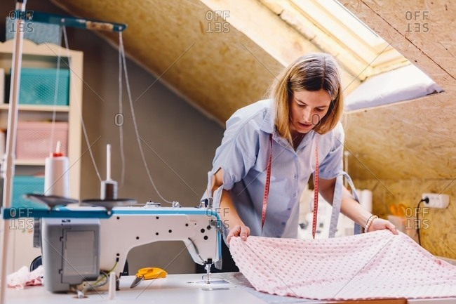 Female tailor examining pink fabric while standing near table with sewing machine in attic workshop