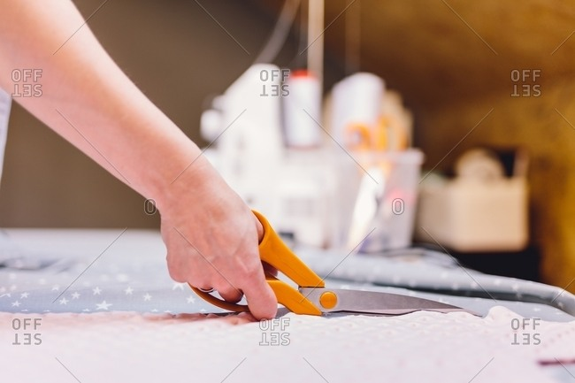 Hand of anonymous tailor using sharp scissors to cut soft cloth on table in workshop