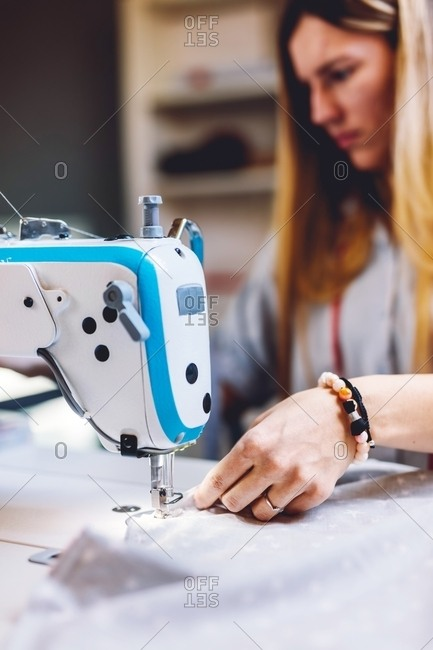 Female tailor smiling and sewing on machine while sitting at table on blurred background of workshop