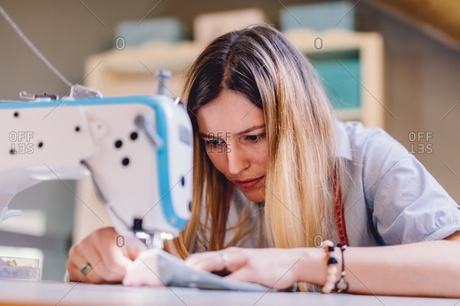 Concentrated female tailor sewing on machine while sitting at table on blurred background of workshop