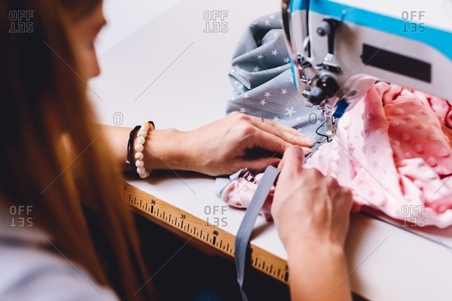 First person view of anonymous female tailor sewing on machine while sitting at table of workshop