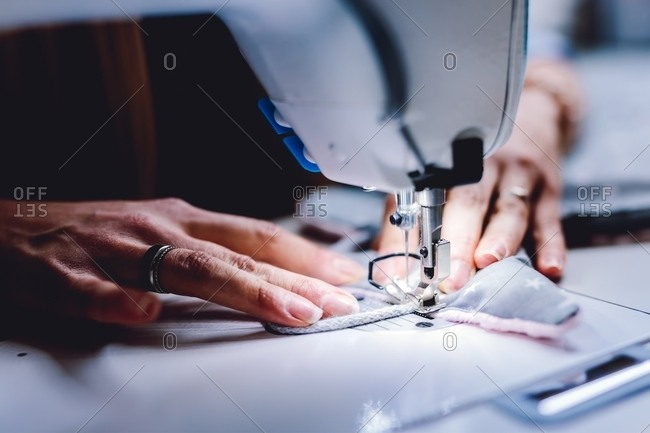 Crop view of hands of female tailor sewing on machine while sitting at table of workshop