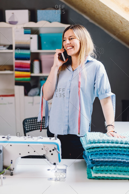 Female tailor on the phone smiling and looking away while standing near sewing machine in workshop