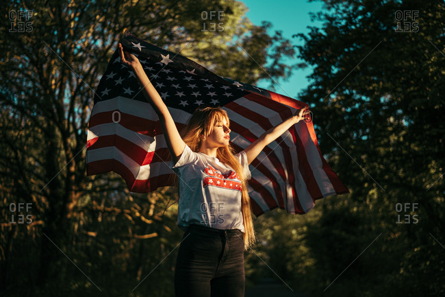 Beautiful young female with closed eyes holding waving USA flag over head