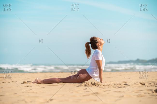 Healthy female doing yoga asana on beach