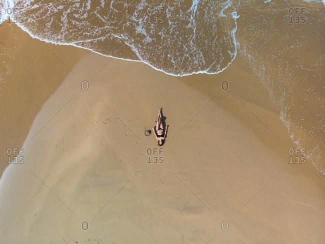 Beautiful female in bikini lying on beach