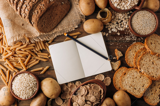 Wholegrain food empty notebook and freshly baked rye bread on table