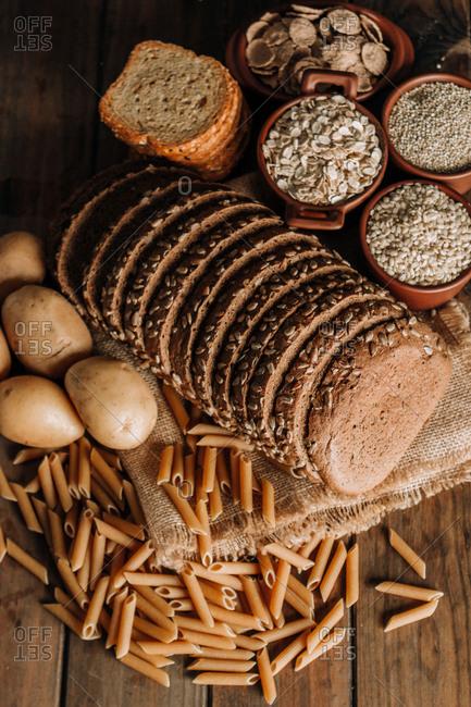 Wholegrain food pasta and freshly baked rye bread on table