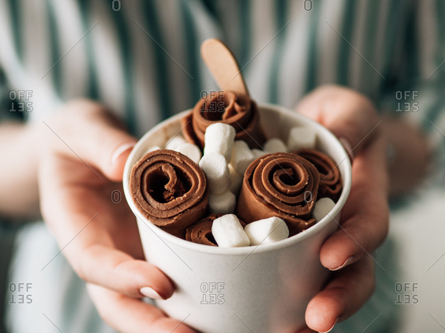 Rolled Cocolate ice cream in cone cup in woman hands. Hand holding cone cup with thai style chocolate rolled ice cream