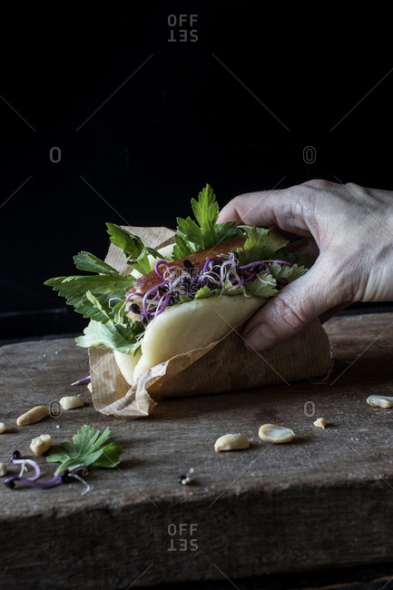 Crop from above of person hands holding delicious Gua Bao sandwich with bacon cooked at low temperature and fresh parsley above board