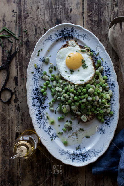From above of served plate with sauteed green peas and fried egg on wooden table
