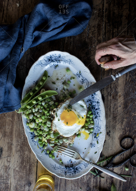 From above person hands eating bread toast with sauteed green peas and fried egg on wooden table