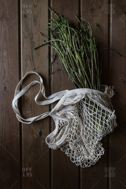 From above of white string bag with big bundle of fresh green asparagus on wooden table