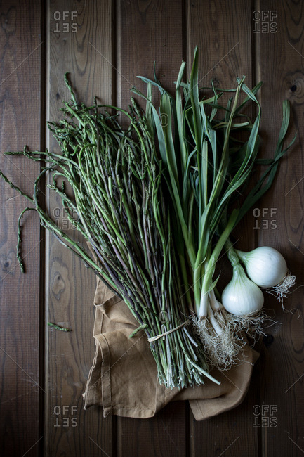 From above of bundle of green asparagus and fresh onion bulbs with green stems on wooden table