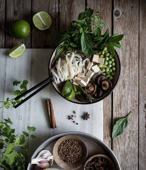 From above of arranged bowls with dry spices and served Pho soup with noodles on marble board