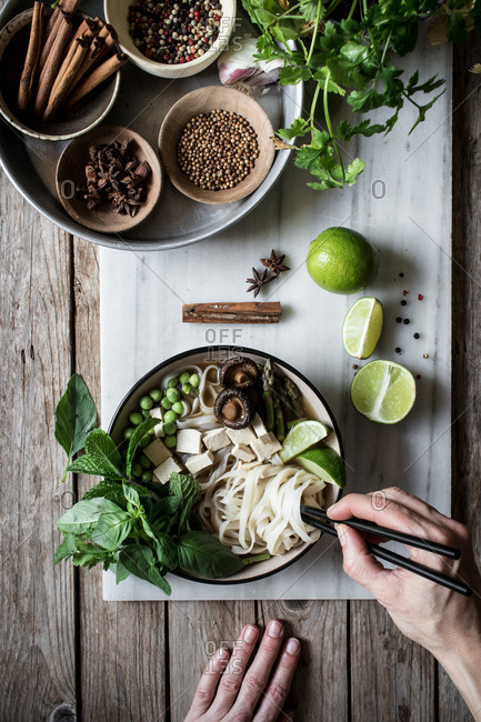 From above person hands with arranged bowls with dry spices and served Pho soup with noodles on marble board