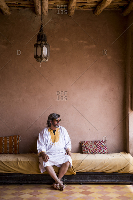 Adult man in long clothes sitting on sofa on terrace with stone fence in oriental style, Morocco