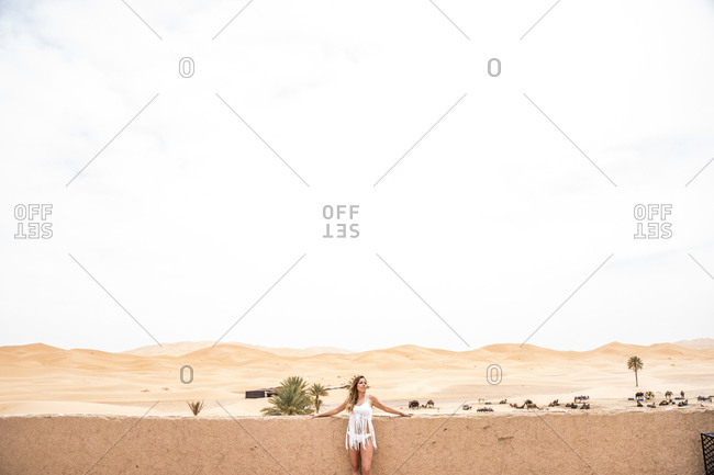 Beautiful young woman in white top leaning on a wall looking away against endless sandy desert, Morocco