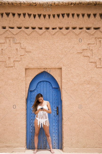 Cheerful young woman wearing white top with bikini and using phone against blue oriental door in stone wall, Morocco