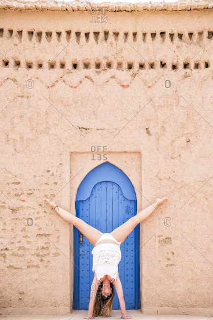Woman in white beachwear showing handstand against oriental blue door in stone wall, Morocco