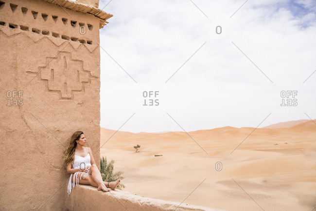Beautiful young woman in white top sitting on stone fence in wind looking away against endless sandy desert, Morocco