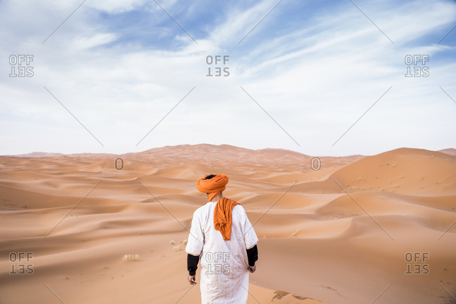 Back view of man wearing long outfit with colorful turban walking on dunes of endless sandy desert, Morocco
