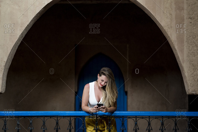 Cheerful beautiful female in stylish outfit smiling and browsing smartphone while leaning on balcony railing of ancient building in Morocco
