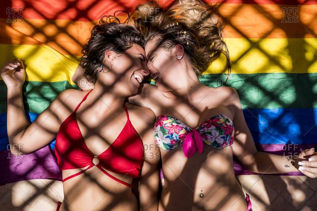 Lesbian couple lying on rainbow flag
