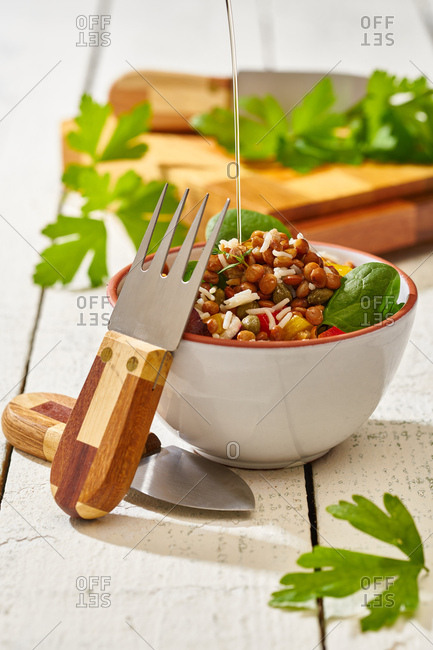 From above appetizing colorful cut vegetable mix with spinach lentils and rice on wooden background