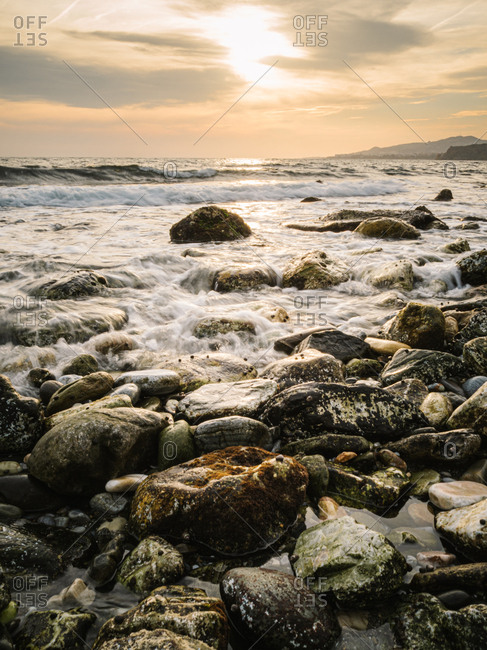 Picturesque view of wet stones on calm seaside against sundown sky