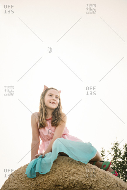 From below of little girl in dress and cat ears sitting on high rock in nature looking away dreamily