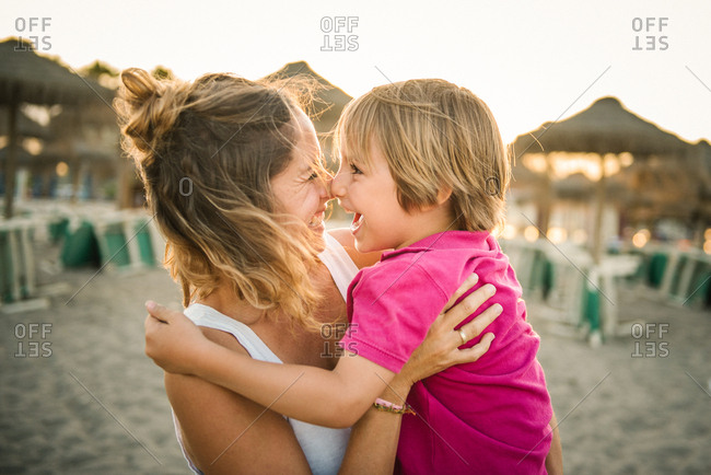 Side view of laughing woman carrying cheerful playful son on hands while rubbing noses on beach in sunset