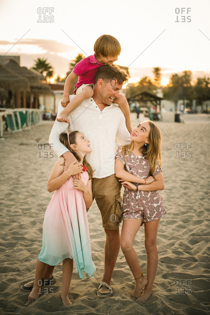 Adult man with laughing boy on shoulders standing with beautiful little girls on beach spending time together