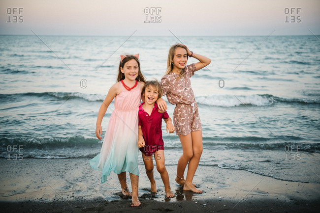 Group of little boy with two sisters playing in shallow wave of water on coast