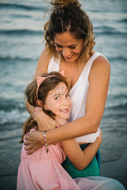 Smiling adult woman with charming girl embracing and looking at camera