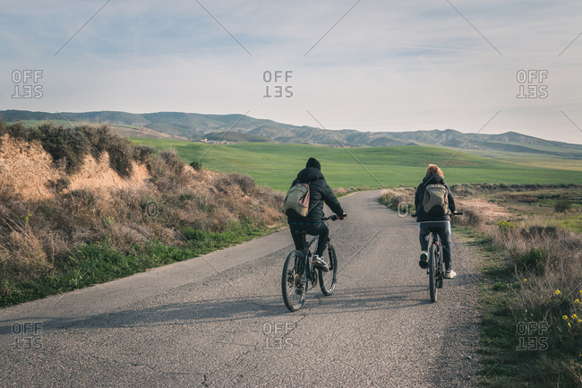 Back view of young men in dark clothes and backpack riding bicycles on empty road winding between stony hills in semi-desert Bardenas Reales Navarra Spain