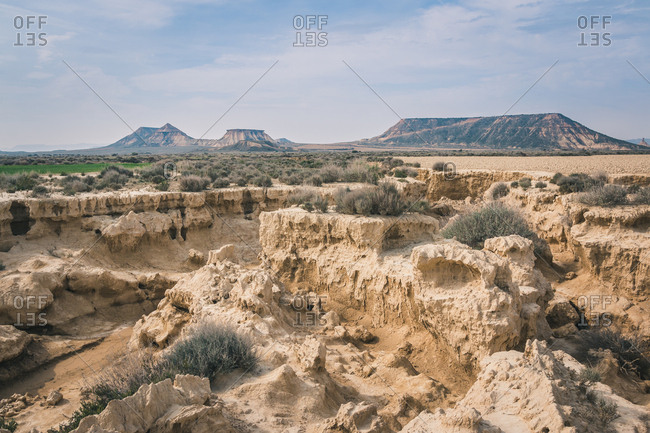 Amazing desert landscape with cracked rocky stones dry vegetation and hills in semi-desert Bardenas Reales Navarra Spain